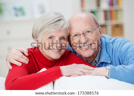 Senior husband and wife smiling happily as they pose together for the camera looking over the back of a comfortable couch in their living room - stock photo