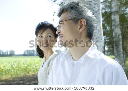 senior husband and wife standing still in front of tree