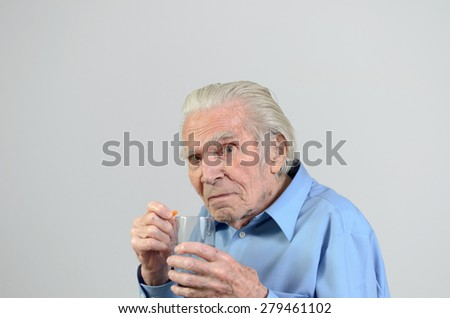 Senior ill man taking the prescribed dose of medicine with a glass of water to treat a chronic disease caused by aging, portrait with copy space on gray