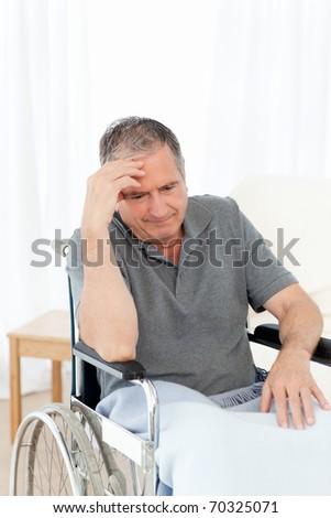 Senior in his wheelchair having a headache at home - stock photo