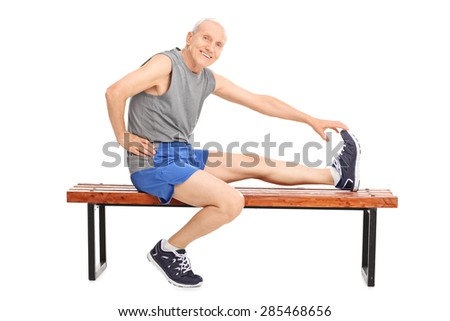 Senior in sportswear sitting on a wooden bench and stretching his leg isolated on white background - stock photo