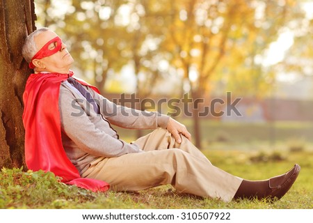 Senior in superhero outfit leaning on tree in park - stock photo