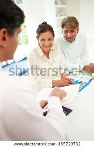 Senior Indian Couple Meeting With Financial Advisor At Home - stock photo