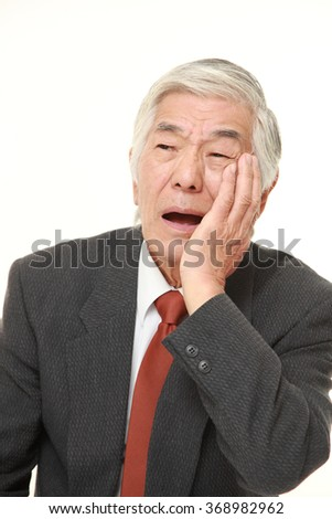 senior Japanese businessman suffers from toothache - stock photo