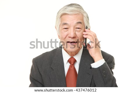 senior Japanese businessman wearing a gray suit talks  with a smart phone  - stock photo