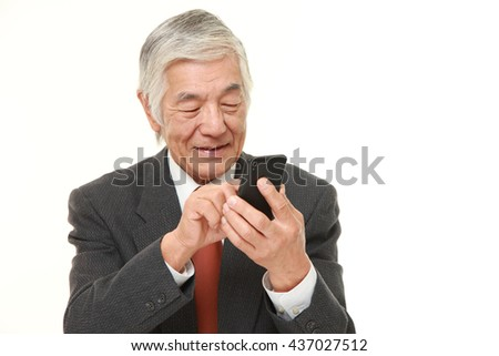 senior Japanese businessman wearing a gray suit  with a smart phone  - stock photo