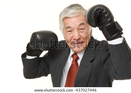 senior Japanese businessman wearing a gray suit with punching glovesthrows in a victory pose