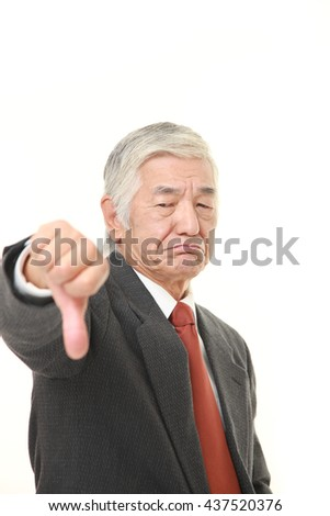 senior Japanese businessman wearing a gray suit with thumbs down gesture
