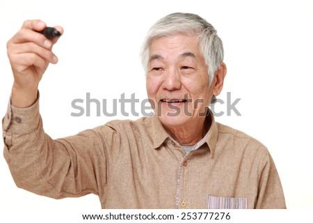 senior Japanese man draw in the air - stock photo