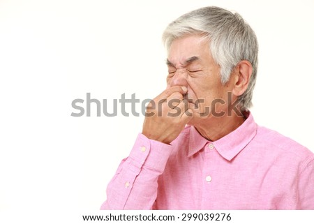 senior Japanese man holding his nose because of a bad smell - stock photo