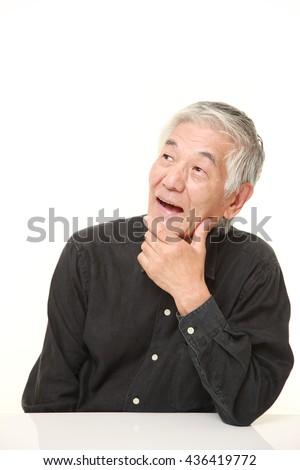 senior Japanese man in a black shirts thinks about something - stock photo
