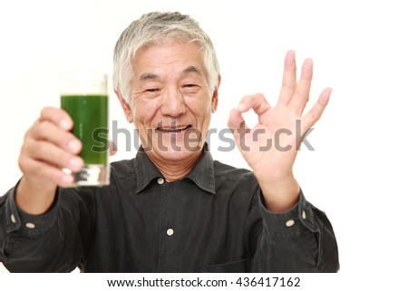 senior Japanese man in a black shirts with green vegetable juice