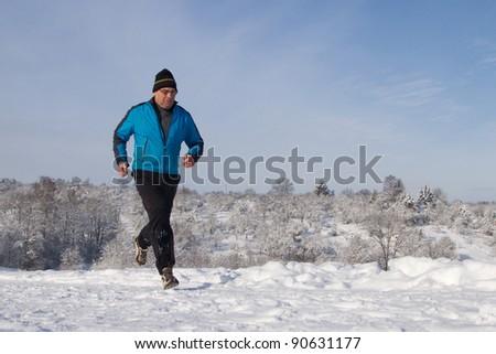 senior jogging in a snowy landscape - stock photo