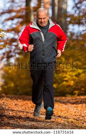 senior jogging in autumn - stock photo