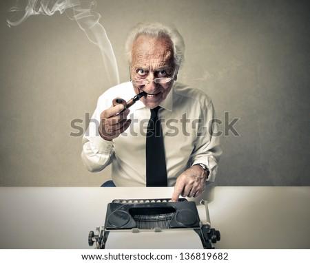 senior journalist writing with a typewriter - stock photo