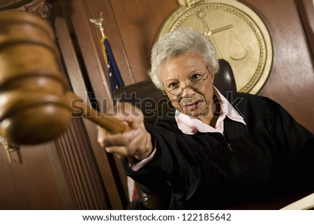 Senior judge pounding after judgment in courtroom - stock photo