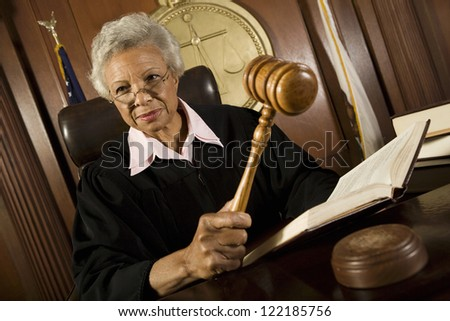 Senior judge sitting with book and mallet in courtroom - stock photo