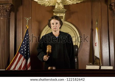 Senior judge standing with mallet in courtroom - stock photo