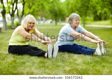 Senior ladies enhancing body flexibility by stretching - stock photo