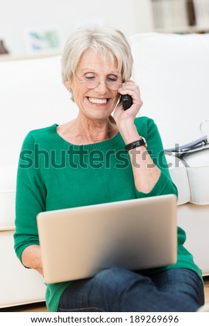 Senior lady chatting on her mobile phone while relaxing on the floor in her living room working on a laptop computer smiling as she listens to the conversation - stock photo