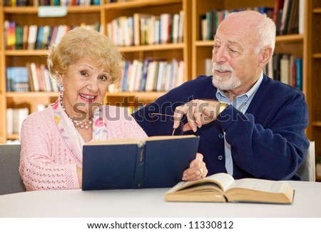 Senior lady happy because she met the man of her dreams in the library.  Focus on the woman. - stock photo