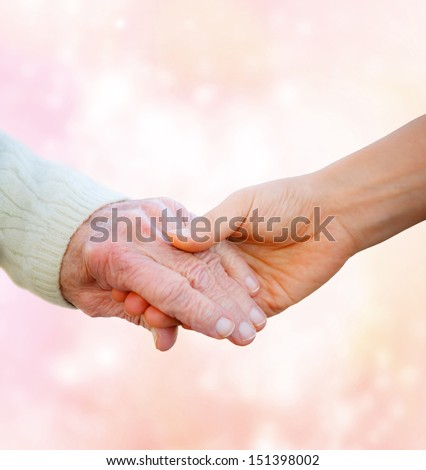 Senior Lady Holding Hands with Young Woman on Pink Lights Background  - stock photo