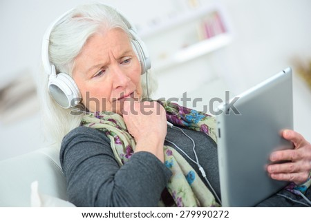 Senior lady listening to music through headphones - stock photo