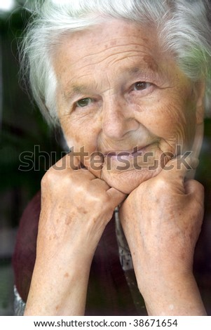 Senior lady looking through the window - stock photo