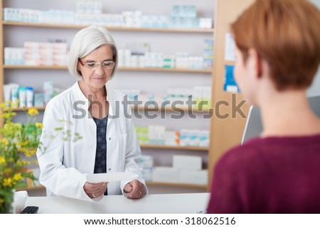 Senior lady pharmacist assisting a patient with prescription medication standing behind the counter reading the script - stock photo