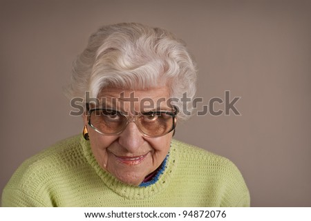 Senior lady portrait, smiling, glasses, with copy space. - stock photo