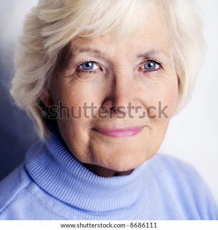 Senior lady portrait with blue pullover and power in her eyes - stock photo
