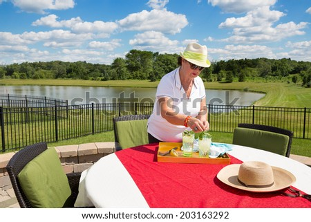Senior lady preparing iced drinks outdoors adding fresh mint and lemon to glasses on a tray on a garden table with red cloth overlooking a tranquil lake and lush countryside - stock photo