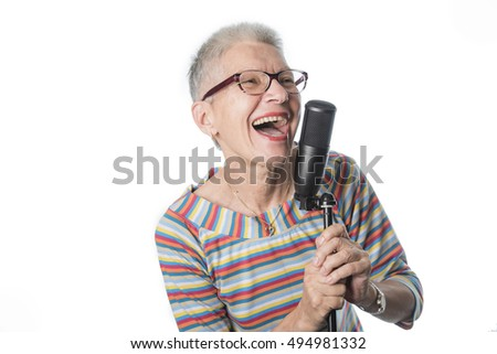 Senior lady singing with a professional microphone, having fun, expressing musical talent