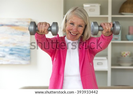 Senior lady smiling at the camera whilst using dumbbells.