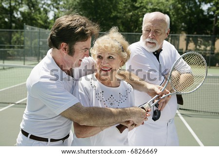 Senior lady taking tennis lessons from a handsome pro while her husband looks on jealously. - stock photo