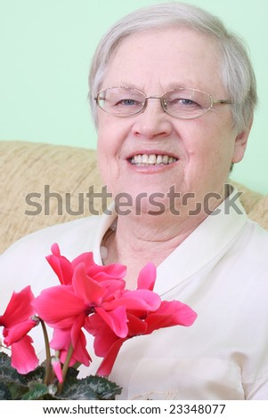 Senior lady with a flower - stock photo
