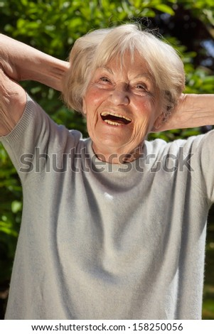 Senior lady with a sense of humor. Senior lady with a good sense of humor having a hearty laugh as she enjoys the sunshine outdoors in her garden on a summer day - stock photo
