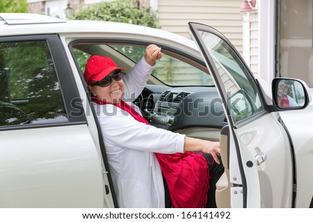 Senior lady with red hat sitting on the passenger seat getting ready close the door and hit the road, she has genuine smile on her face - stock photo