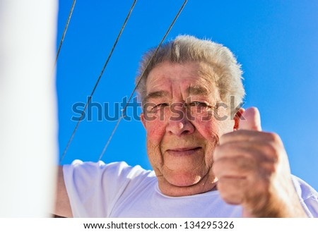 Senior lifts the thumbs up in bright blue sky - stock photo