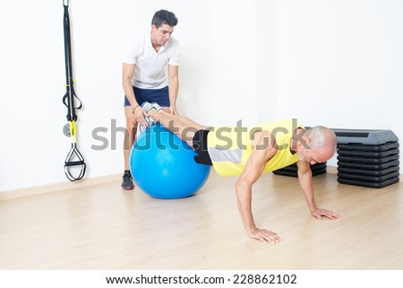 senior makes suspension training with coach - stock photo