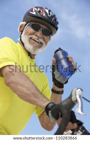 Senior male bicyclist holding water bottle