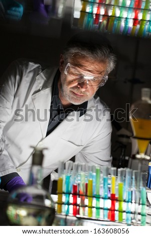 Senior male chemist working late hours in science research laboratory (chemistry, analytical, organic, structural, biochemistry, genetics, forensics, microbiology..) - stock photo