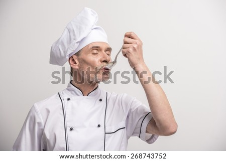 Senior male chief cook in uniform eating with spoon a  on grey background. - stock photo