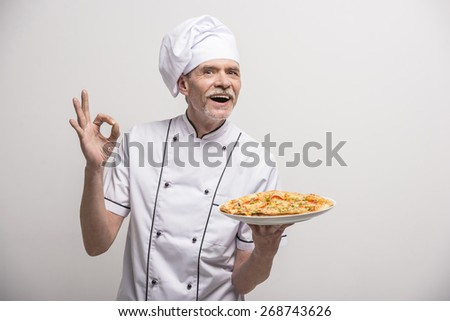 Senior male chief cook in uniform gesturing okay sign  and holding pizza on grey background.