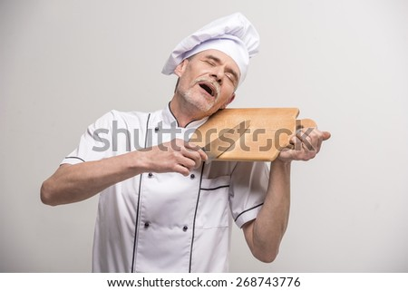 Senior male chief cook in uniform holding knife and  chopping board a  on grey background. - stock photo