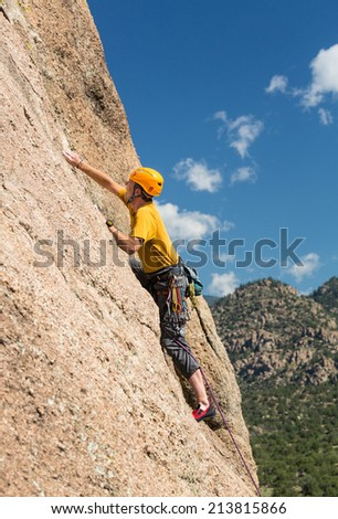 Senior male climber well equipped with cams and caribiners climbing on Turtle Rocks near Buena Vista Colorado - stock photo