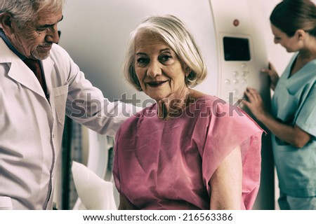 Senior male doctor and female assistant examining woman in 70s with CT scanner. Computerised tomography. - stock photo
