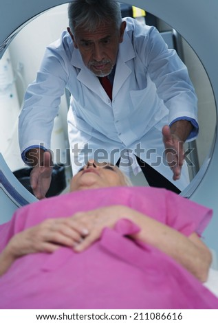 Senior male doctor examining woman in 70s with CT scanner. - stock photo