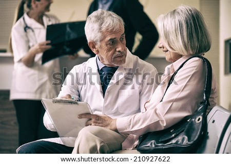 Senior male doctor showing medical results to his female woman patient with x-ray analysis in background. - stock photo