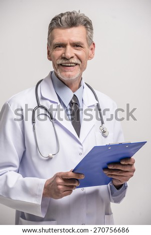 Senior male doctor standing with folder on grey background. - stock photo